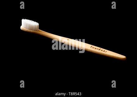 Bamboo tooth brush on a black background. Eco friendly hygiene product. - Stock Image