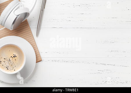 Office workplace table with coffee cup, headphones and supplies. Flat lay. Top view with space for your goals - Stock Image