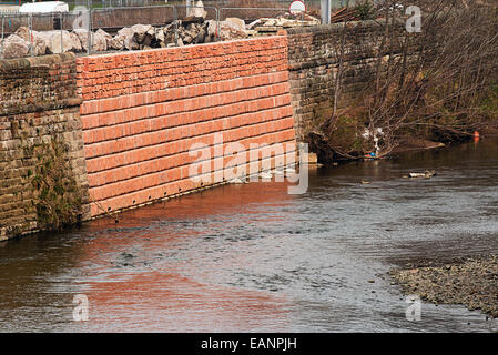 Damaged flood wall that has been repaired due to a recent breach broke the banks of the river during a storm. - Stock Image