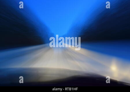 Pov shot through the windshield of a car driving on a snow-covered country lane through a forest at dusk - Stock Image