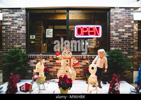 Girl with Christmas decorations next to open restaurant - Stock Image