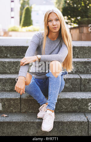 teenage girl with long blond hair and distressed jeans sitting on steps outside - urban lifestyle or street fashion concept - Stock Image