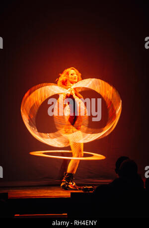 Woman performing on stage, spinning illuminated rings - Stock Image