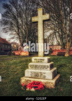 War memorial outside village parish church, Yorkshire Dales, England, UK - Stock Image