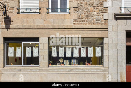 Lace cloths hanging up in a restaurant window at Fougères, Brittany, France - Stock Image