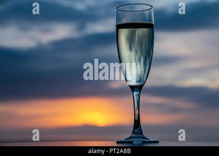 Glass of champagne overlooking a sunset sky - Stock Image