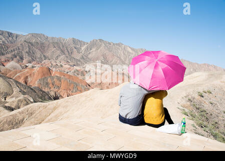 Couple enjoying the view protected by an umbrella at Zhangye-Danxia-Geopark, Gansu Province, China - Stock Image