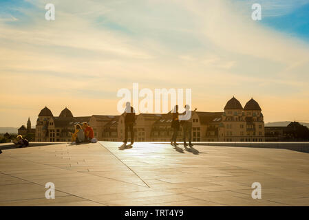 Oslo Opera House, view on a summer evening of tourists on the roof of the Oslo Opera House (Operahuset) looking across the city, Norway. - Stock Image