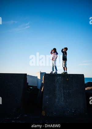 Boy and girl stand on harbour wall and look out to sea. - Stock Image