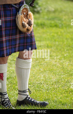 Bagpipe player dressed in Scottish National Dress including kilt and sporran with space for your text - Stock Image