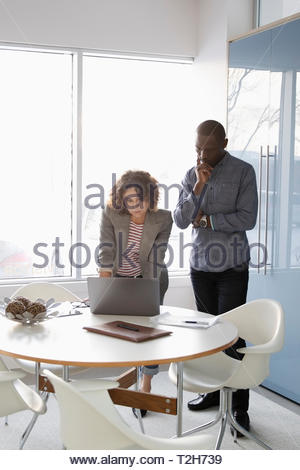 Business people working at laptop in conference room - Stock Image