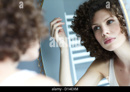 young woman checking her hair in the mirror - Stock Image