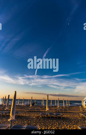 Sunbeds on the beach with yellow closed umbrellass, colorful sky and the sea behind. Sunrise time. Jesolo, Italy. - Stock Image