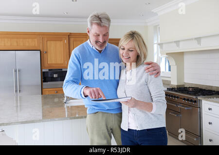 Mature Couple Viewing New Home Standing In Kitchen Looking At Brochure - Stock Image
