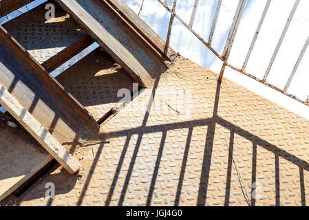 Shadows from old metal railing cast from strong daylight - Stock Image