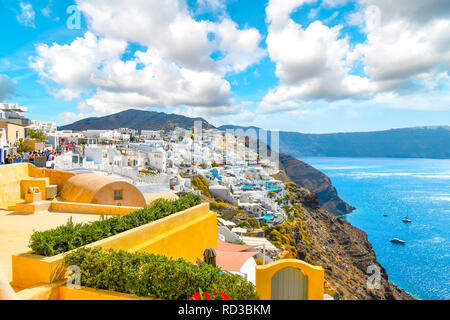 A scenic view of the Santorini caldera and the Aegean Sea from a resort terrace as tourists walk the main street in the hillside village of Oia Greece - Stock Image