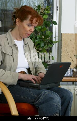 Adult woman over 40 using laptop at home in 2003 - Stock Image