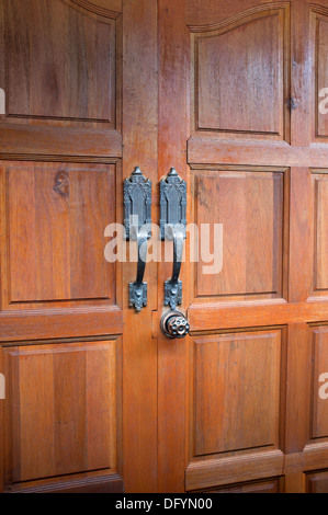 Two brown wooden doors with Thai designed ornamental handles. - Stock Image