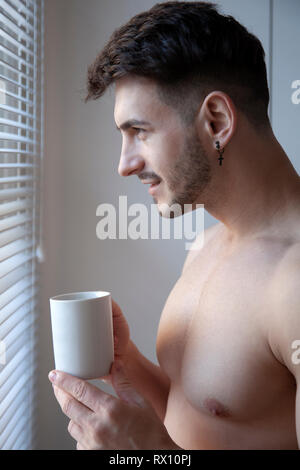 Topless Man Drinking Beverage By Window - Stock Image