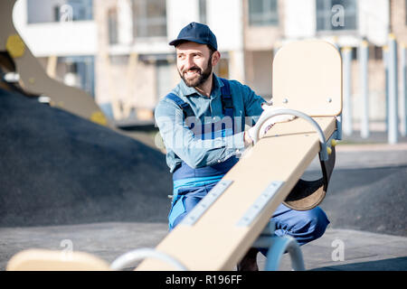 Handsome workman in uniform mounting kids swing on the playground outdoors - Stock Image