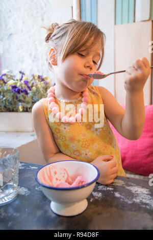 Three years old blonde little girl with yellow dress an necklace eating and enjoying strawberry ice cream with spoon from bowl, sitting indoor in rest - Stock Image