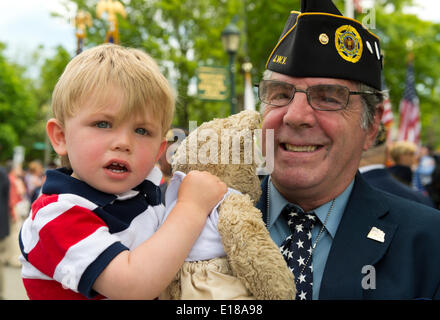 Merrick, New York, U.S. - May 26, 2014 - GARRY GLICK, a member of American Legion Post 1282, holds his grandson MAX, almost 2, after the veteran marched in the Merrick Memorial Day Parade, which honored those who died in war while serving in the United States military. © Ann E Parry/Alamy Live News Credit:  Ann E Parry/Alamy Live News - Stock Image