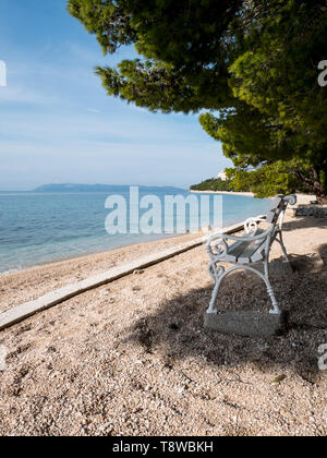 Wooden bench on beach with sea view in Tucepi, Croatia - Stock Image