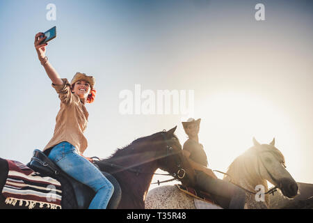Happy couple on vacation take picture selfie with smart phone during a ride with horses in outdoor leisure activity together - clear sky and sunset li - Stock Image