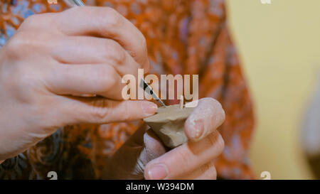 Woman potter making ceramic souvenir penny whistle in pottery workshop - Stock Image