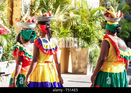 Cartagena Colombia Old Walled City Center centre Centro Afro Caribbean Palenquera woman fruit vendor traditional costume carrying bowl on head cultura - Stock Image