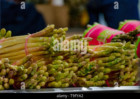 bunches of fresh raw asparagus vegetables on market, healthy and tasty vegetarian food - Stock Image