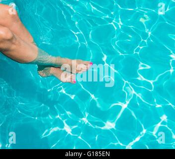 Woman soaking feet in swimming pool - Stock Image