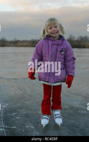 Litte girl with ice skates standing on ice happy look at camera, full body, west European girl - Stock Image