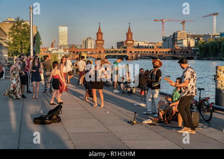 sunset at riverside Spree, Berlin wall, live band, background Oberbaum Bridge, Oberbaumbruecke, Friedrichshain, Berlin, Germany - Stock Image