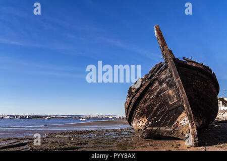 Old traditional Tagus River wooden sailboat burnt and wrecked in Seixal Bay, Portugal - Stock Image