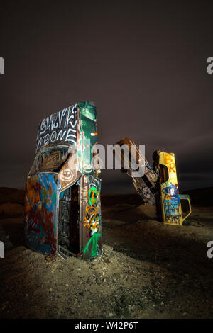 Two cars and a bus stand upright in the desert at night at the International Car Forest of the Last Church in Goldfield, Nevada. - Stock Image