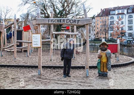 Berlin,Mitte,Moabit.senior elderly man in Children's playground & wooden sculpture of Fisherman holding fish. - Stock Image