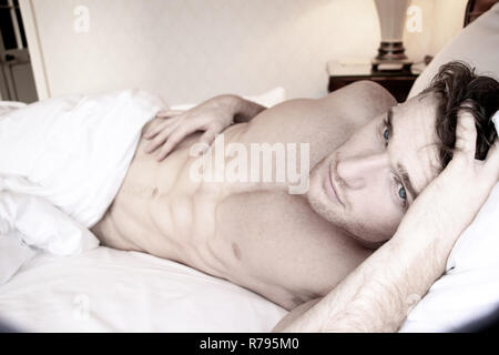 Good looking naked man with six pack abs and blue eyes eyes lying naked in bed - Stock Image