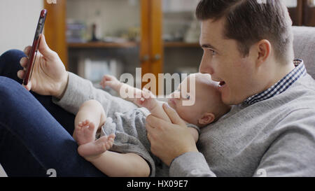 Close up profile of smiling father taking smartphone selfie with baby daughter on sofa - Stock Image