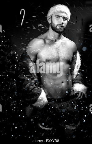 Handsome shirtless male santa with open jacket revealing pecs and defined body. - Stock Image