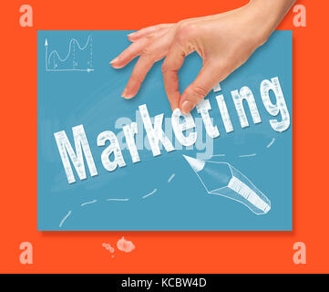 A hand picking up a Marketing concept on a colorful drawing board - Stock Image