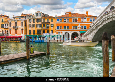 A man with a backpack sits on a dock, as tourists enjoy canal front cafes and a boat drives under the Rialto Bridge in Venice, Italy - Stock Image