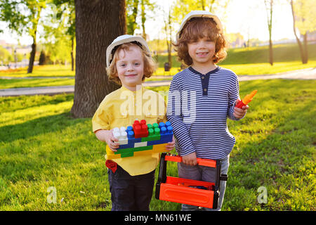 boys in white construction helmets play in workers with toy tools. - Stock Image