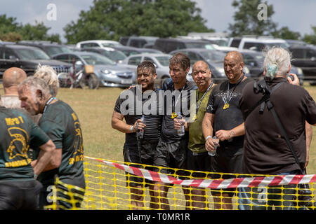 Group of four muddy men at the end of a mud run - Stock Image