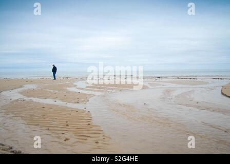 Walker on a Normandy beach, France - Stock Image