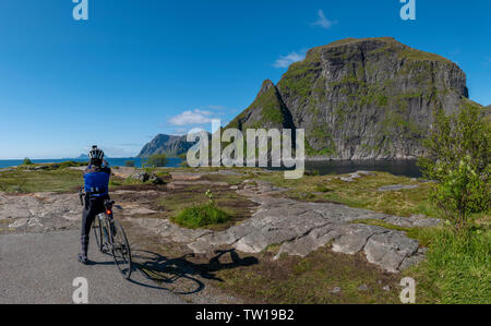 Female cyclist at southern tip of the Lofoten Islands, Norway. - Stock Image