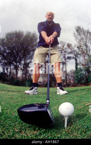Close up of golfer hitting ball with fish eye lens - Stock Image