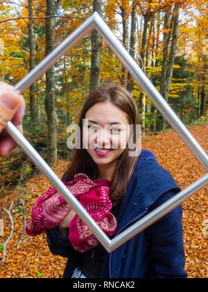 Pretty teen girl is smiling at camera framed by picture flramed hand held before camera giggle giggling - Stock Image