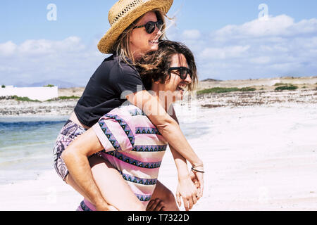 People having fun in outdoor leisure activity with cheerful man carrying beautiful young woman at the beach - blue sea and sky in background for nice  - Stock Image