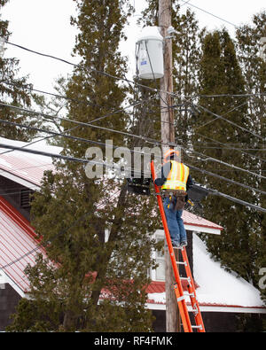 A man on a ladder working on fiber optic cable connections in Speculator, NY USA on a cold winter day. - Stock Image